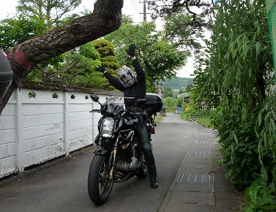 バイクにまたがって両手を上げる