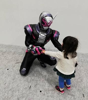 仮面ライダーと握手する娘